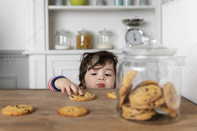 Young boy reaching at cookies on kitchen table