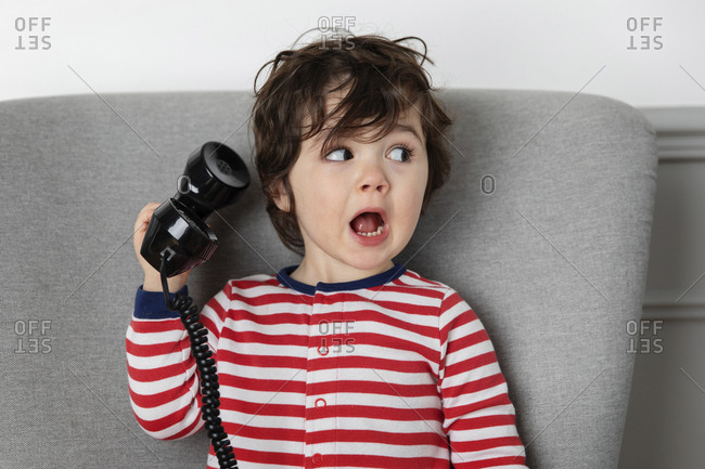 Young child holding vintage phone with funny surprised expression