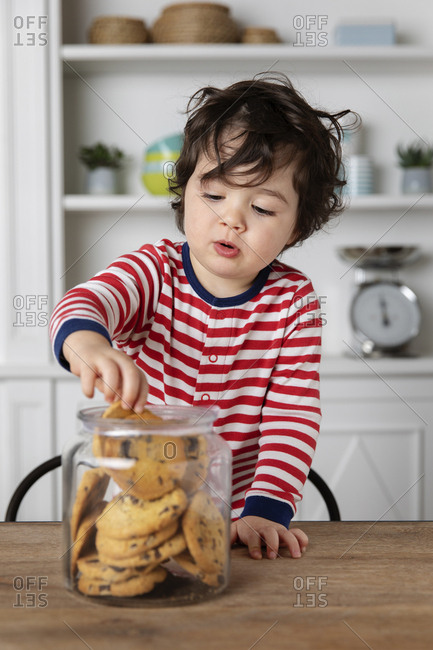 Cute young child reaching into a cookie jar