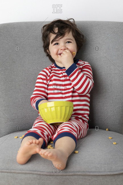 Smiling toddler sitting on sofa eating cereal with hands