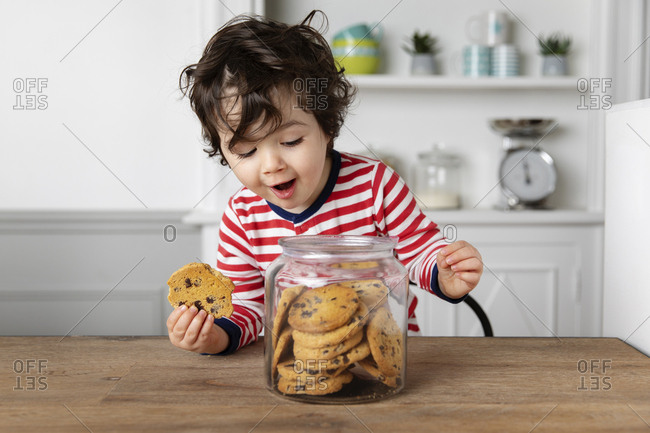 Cute toddler holding a cookie while looking into cookie jar