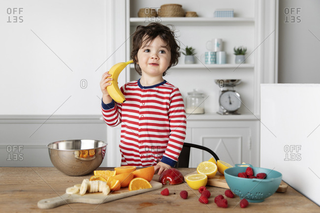 Toddler at kitchen table with fruits pretending to phone with a banana