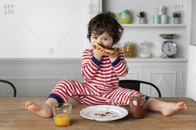 Toddler sitting on kitchen table eating bread with chocolate