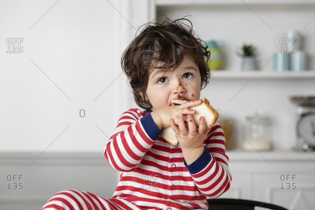 Toddler with chocolate smeared face eating slice of bread