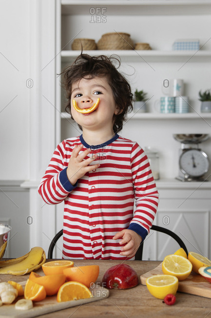 Funny toddler playing with fruits in kitchen with orange peel in mouth
