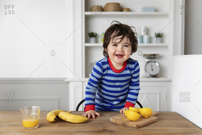 Smiling little boy at kitchen table with bananas and lemons