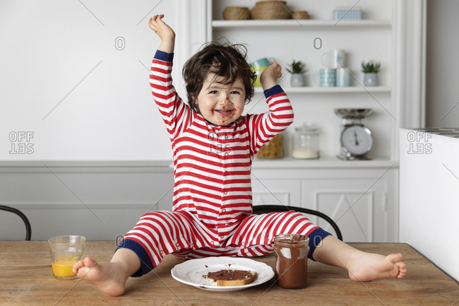 Happy toddler with chocolate smeared face sitting on kitchen table