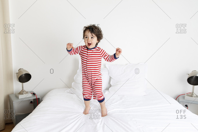 Happy toddler in striped pajamas jumping on bed