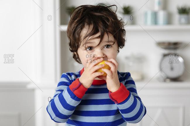 Close up of young boy biting a lemon