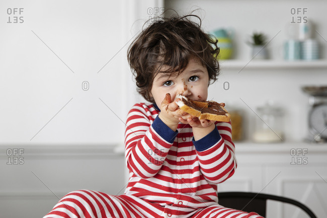 Little boy eating bread with chocolate