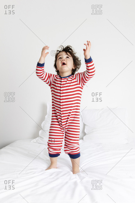 Cute little boy standing on white bed looking up with arms raised