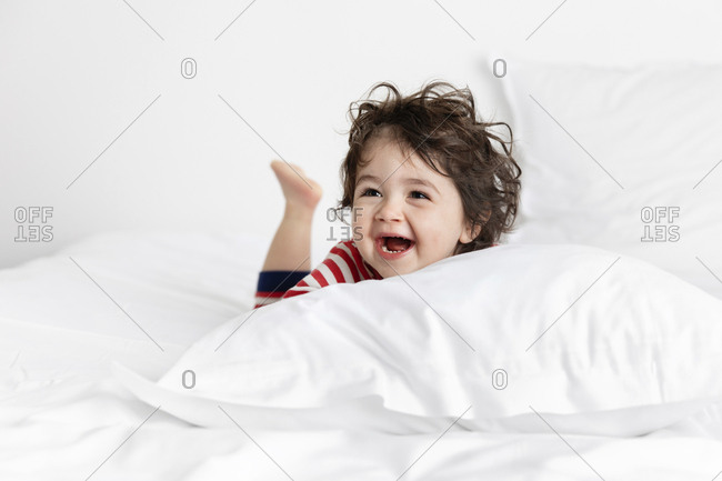 Laughing toddler on white bed near pillow