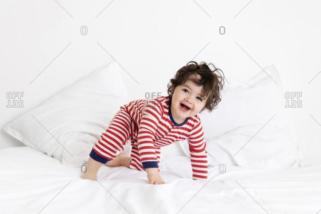 Laughing toddler crawling on white bed