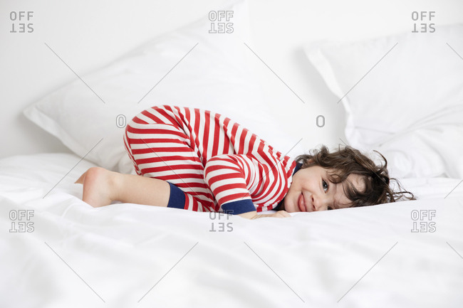 Smiling young child in pajamas resting on white bed sticking tongue