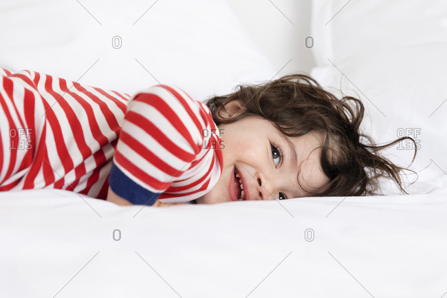Smiling little boy in pajamas lying on white bed with ruffled hair