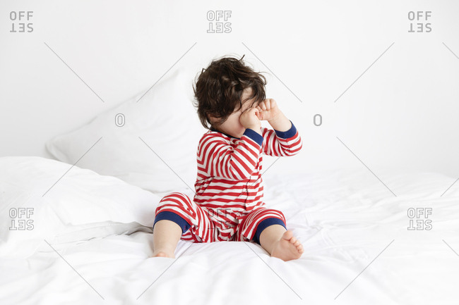 Sleepy toddler wearing pajamas sitting on white bed rubbing eyes