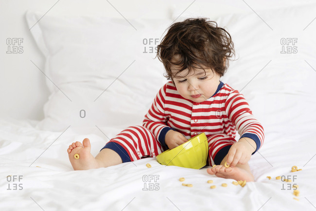 Toddler making mess with cereal on white bed
