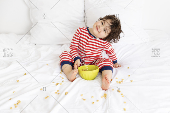 Smiling young boy on white bed making mess with cereal bowl