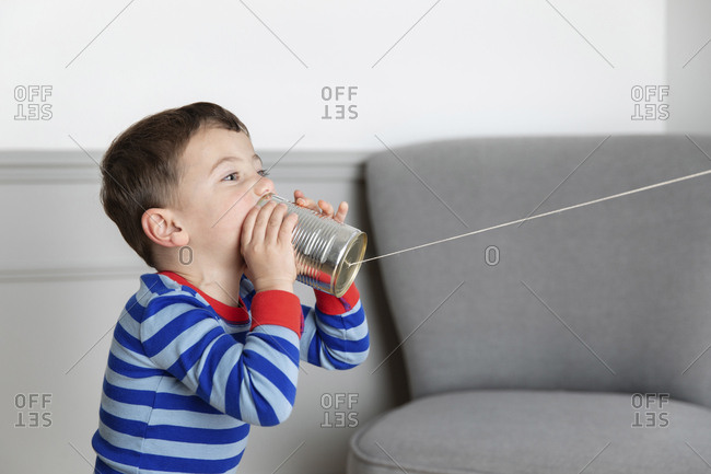 Young boy playing with tin can telephone