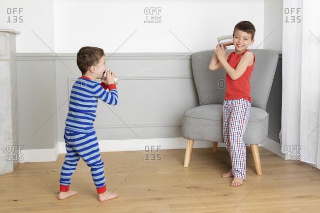 Two happy young boys playing with tin can phone