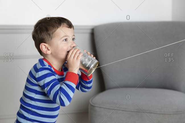 Young boy talking in tin can phone