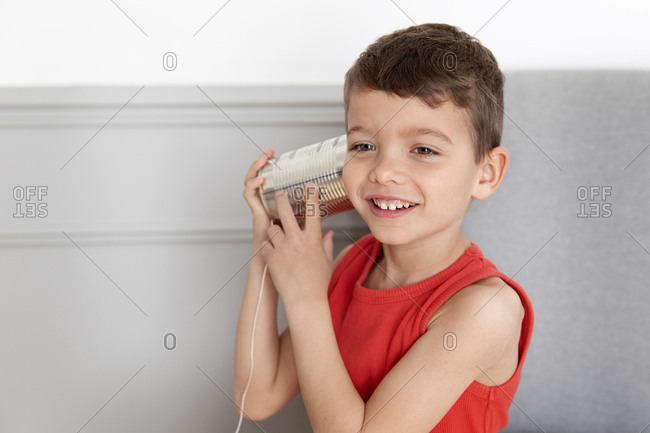 Smiling boy listening to tin can telephone