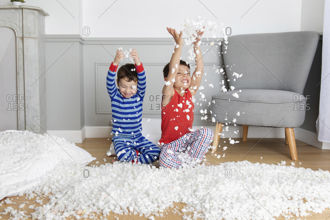 Young boys making mess with pillow stuffing