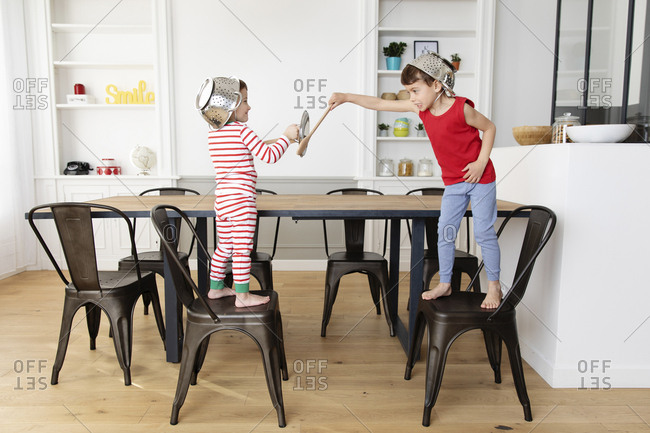 Young boys playing swords with wooden utensils in kitchen