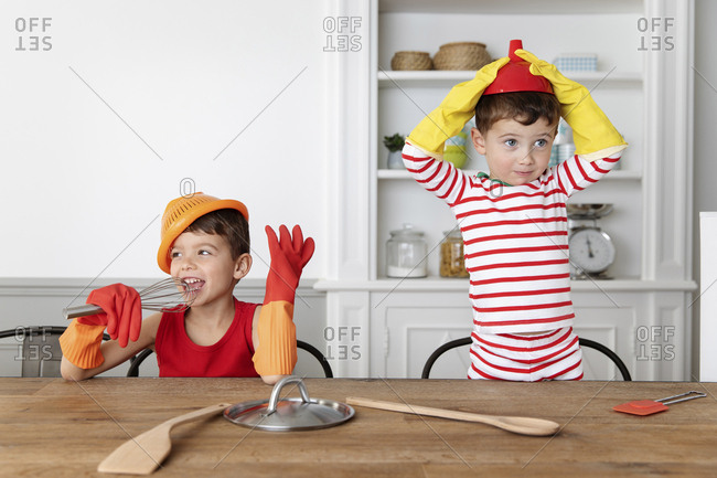 Goofy young boys playing with utensils in the kitchen