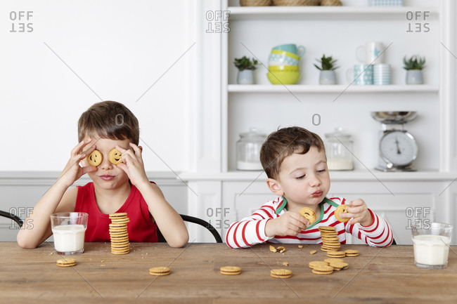 Brothers having snack at kitchen table playing with cookies