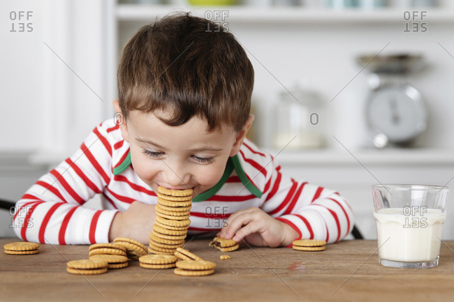 Young boy at kitchen table eating stack of cookies