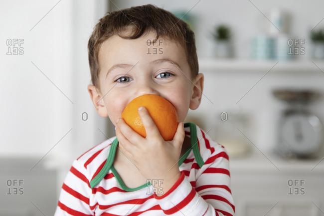 Happy little boy biting in an orange