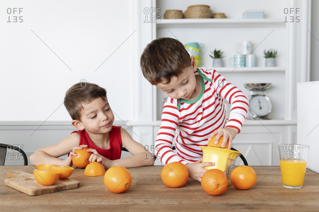 Young boys juicing oranges together
