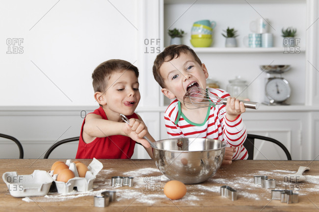 Young boys baking together at kitchen table licking whisk