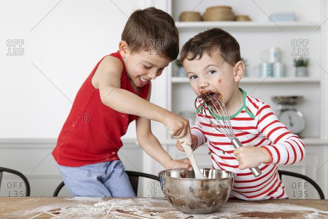 Children baking together at kitchen table licking whisk