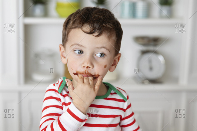 Young boy with messy chocolate face licking fingers