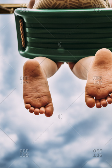 Young kid on swing with dirty feet