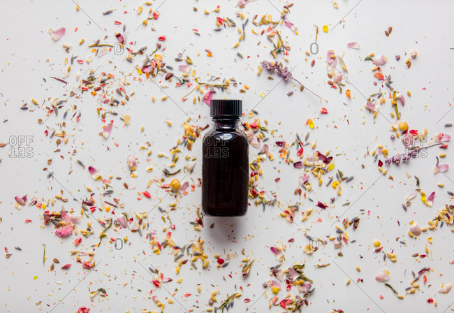 Black glass bottle with lavender flower petals on a white background
