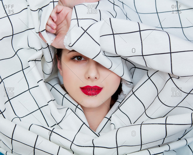 Portrait of a young girl with red lipstick shrouded in checkered fabric