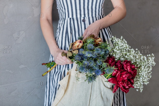 Female with tote bag and gypsophila paniculata, eryngium, and peonies flowers on white background.