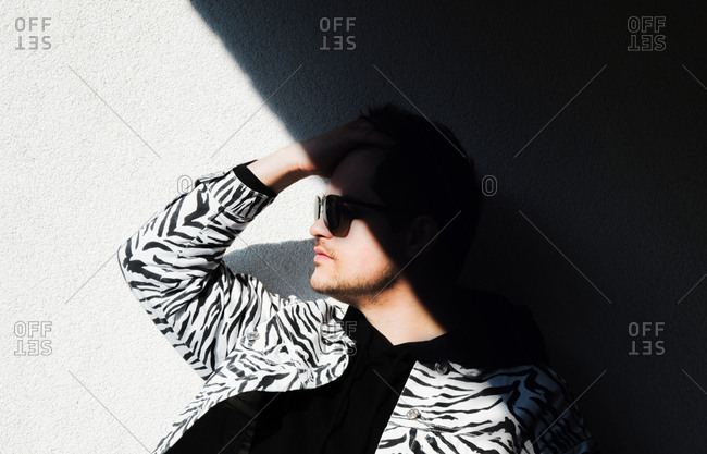 Young man in zebra print clothes and black sunglasses stays in the shadow