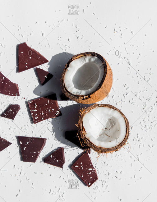 Coconut and dark chocolate on a white background with shadows