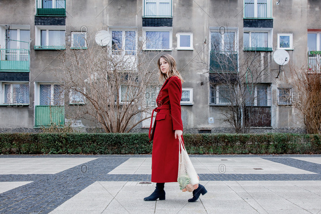 Stylish woman in a red coat walks home after shopping. Eastern Europe