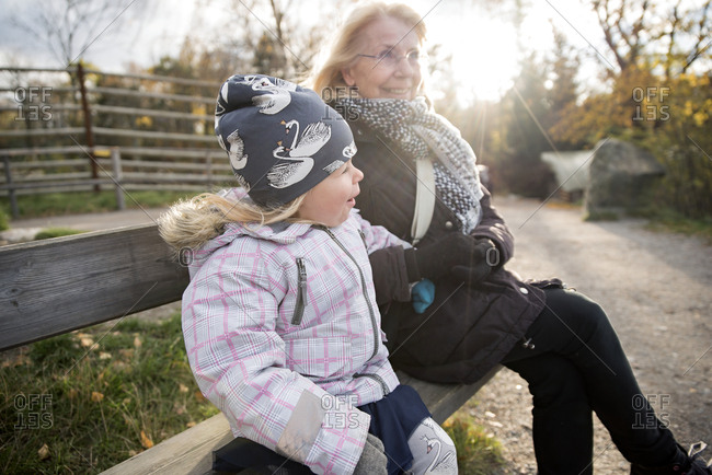 Grandmother and granddaughter sitting on bench