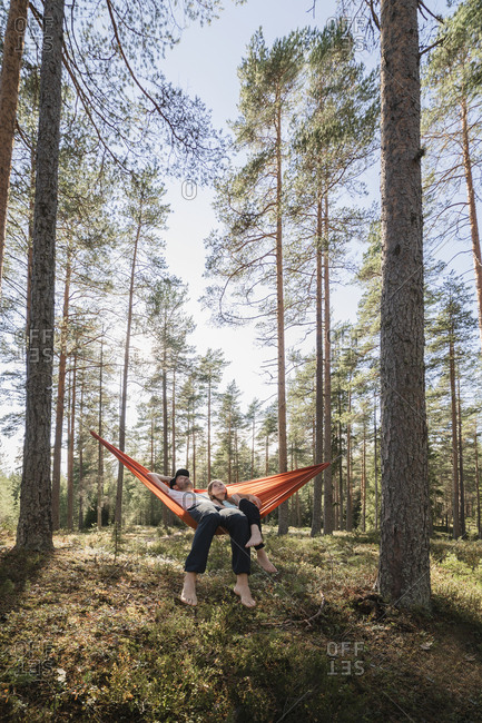 Father and daughter relaxing in hammock in forest