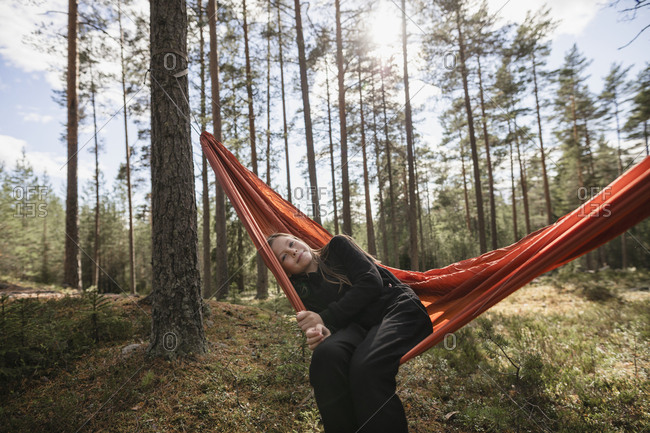 Young woman sitting in hammock in forest