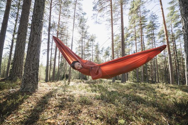 Teenage girl lying in hammock in forest