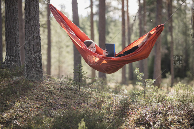 Teenage girl reading book in hammock in forest