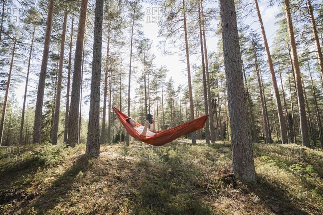 Man reading book in hammock in forest