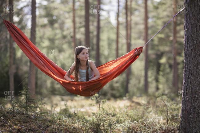 Teenage girl sitting in hammock in forest